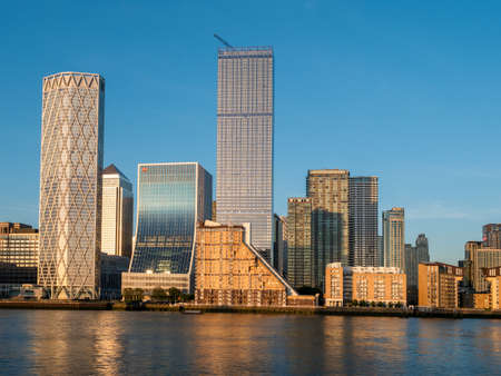 London, England, UK - May, 27, 2020: Canary Wharf district buildings of London illuminated at sunset against the blue sky
