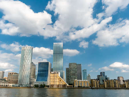 London, England, UK - May  27, 2020: Financial district buildings in Canary Wharf area of London in a daytime against cloudy blue sky