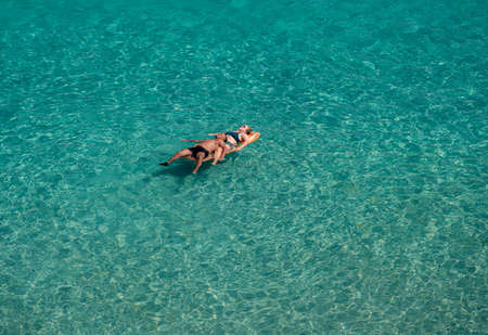 Lecce, Italy - August 11, 2018: Couple of people floating on the blue clear sea in a sunny day in summer holiday on the coast of Lecce