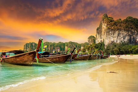 Traditional boats on Railay beach at sunset on the coast of Krabi region in Thailand