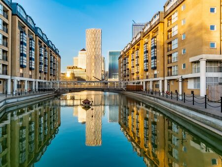 Financial district buildings in Canary Wharf area of London reflected in a lake