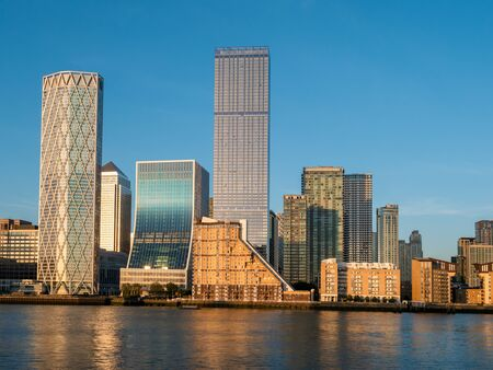 Financial district buildings in Canary Wharf area of London illuminated at sunset against the blue sky Imagens