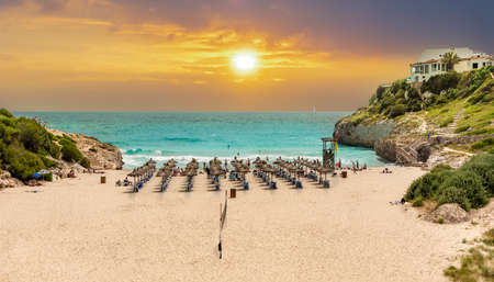 Beautiful vibrant sunrise on the beach on Cala Domingos playa de Mallorca in summer holiday, Spain Imagens
