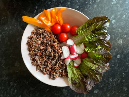 Top view of a delicious vegetarian and vegan meal with spinach leaves, red cherry tomatoes and whole wheat bulgur Imagens