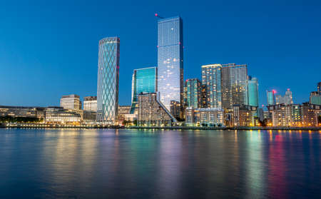 Financial district of London city Canary Wharf reflected on the Thames river at blue hour in England Imagens