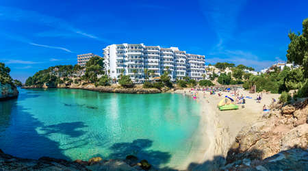 Panoramic view of Cala Ferrera beach with people on seaside in summer holiday on Mallorca island, Spain