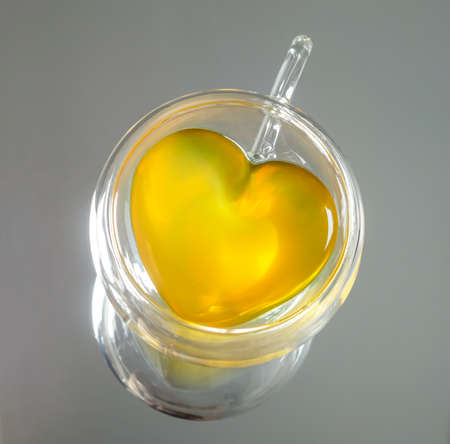Top view of a transparent heart-shaped teacup with yellow tea liquid