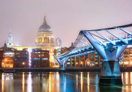 Millennium bridge and the famous Saint Paul's Cathedral in the city of London illuminated in evening lights