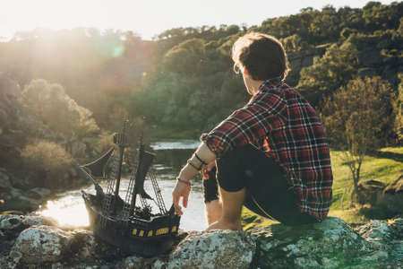 A young boy with his toy pirate ship looking at sunset in the middle of nature