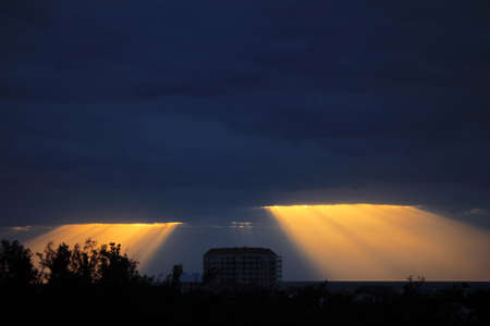 flare stack: Golden sun rays bursting through the dark blue clouds Stock Photo