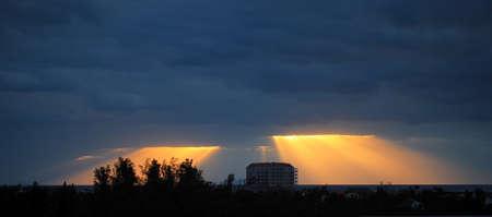scarcity: Golden sun rays bursting through the dark blue clouds Stock Photo