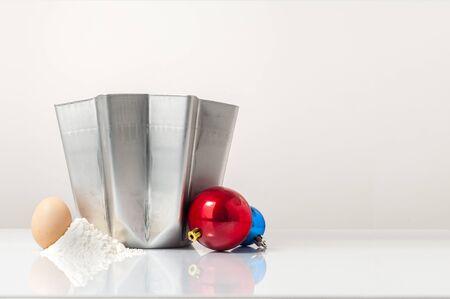 A cover shot for a pandoro recipe: a pandoro mold with egg, flour and a couple of Christmas balls Zdjęcie Seryjne
