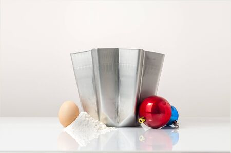 typical: A cover shot for a pandoro recipe: a pandoro mold with egg, flour and a couple of Christmas balls Stock Photo
