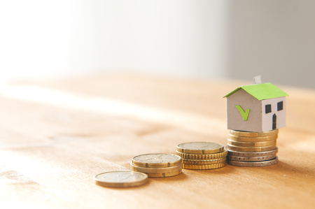 A paper house on a coin pile and a stair made of coin: mortgage and loan concept Stockfoto