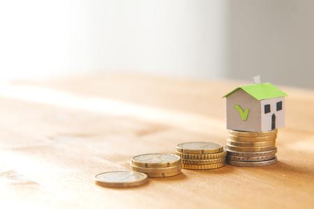 Une maison en papier sur une pile de pièces de monnaie et un escalier en pièces de monnaie: concept d?hypothèque et de prêt Banque d'images
