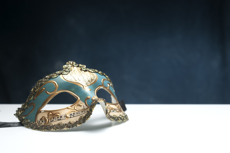Blue venetian mask on white table with blue background and copy space 写真素材