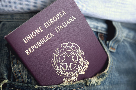 An italian passport out of the pocket of denim trousers Stok Fotoğraf
