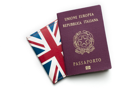 An italian passport on top of a british card holder on white background