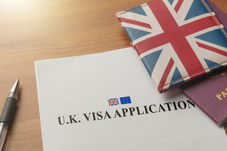 Visa application on desktop with passport and union jack wallet