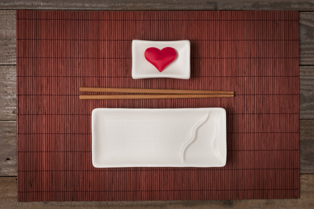 Ceramic plate for sushi and japanese food with chopstick and bowl for soy sauce with a heart inside on bamboo mat top view