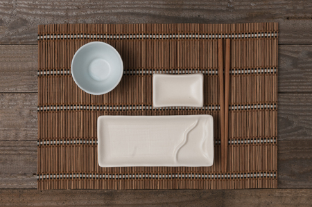 Ceramic plate for sushi and japanese food with chopstick and bowl for soy sauce on bamboo mat top view Reklamní fotografie