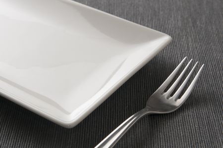 Square ceramic plate and a fork on a table