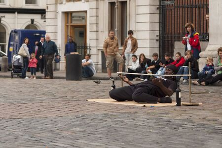 LONDON, UK - SEPTEMBERT 01, 2009: A street artist in Covent Garden entertains the audience with the game of limbo
