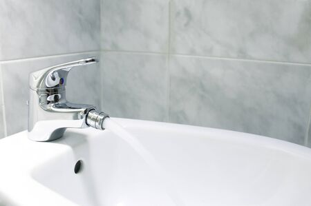 Detail of the faucet of a bidet with running water.The bidet was invented in France in the 1700s