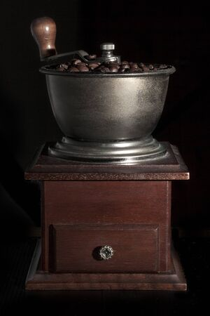 Coffee grinder full of coffee beans on black background
