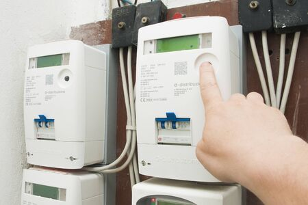 Milano, Italy - July 12, 2019 - Man checks the consumption on the new e-distributione (enel) electricity meter Redakční
