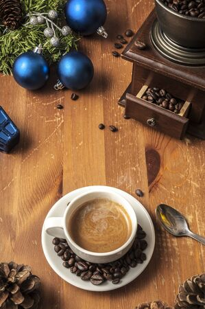 Cup of coffee sorrounded by Christmas decorations, a coffee grinder and coffee beans