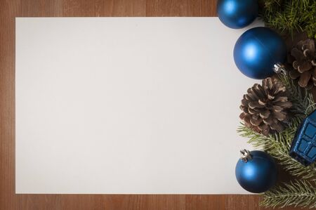 Christmas blue and green decorations on wooden table with big white card as copy space