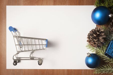 Christmas blue and green decorations on wooden table and a big white card with shopping cart on it as copy space