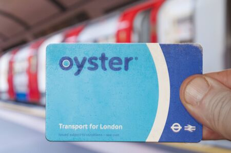 London, Uk - July 18 2019 - London Tube passenger hol a Oyster Card in front of underground train
