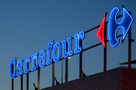 MASSA, ITALY - August 05, 2019 - The illuminated neon sign of the French supermarket chain Carrefour at sunset Redactioneel
