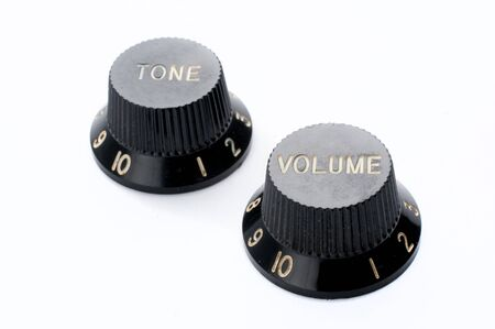 Vintage black guitar volume and tone knobs on white background
