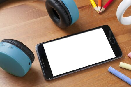Blank screen smartphone on wooden table next to a pair of wireless earphones, some pencils and some chalks