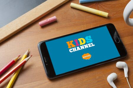 Smartphone ready to stream a kids channel on a table with pencils, a slate with some colored chalks and a pair of earphones