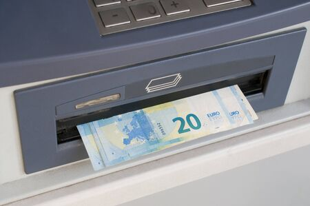 Euro banknotes dispensed from an ATM machine (bancomat)