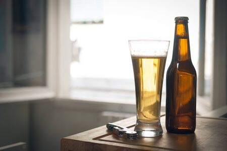 Bottle and glass of beer and a corkscrew on wooden surface with blurred background and cinematic color grading