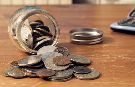Coin jar overturned on the table with cap and calculator in the background. This image can be used to represent different concepts related to money.