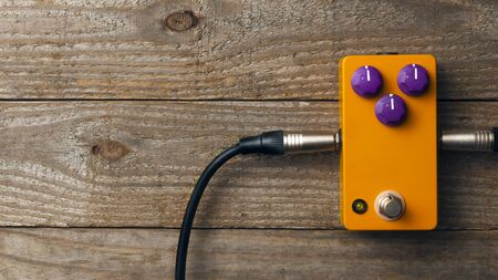 Blank orange guitar pedal with purple knobs and plugged jacks on wooden floor