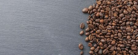 Fresh roasted coffee beans on blue stone table, lot of copy space
