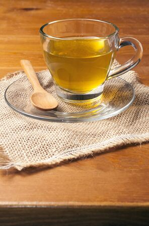 Green tea on a glass cup on wooden table