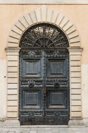 Black old wood portal with iron and marble decorations at the main entrance of the fine art academy in Carrara, Italy