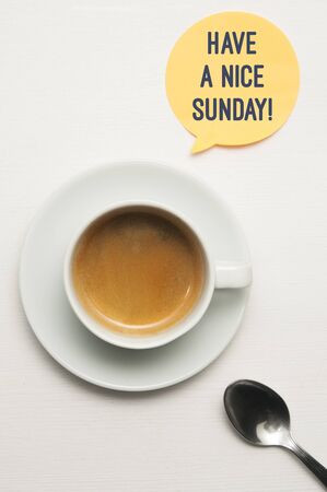 Have a nice sunday concept: a cup of coffee on a white wooden table and a balloon with the text: have a nice sunday