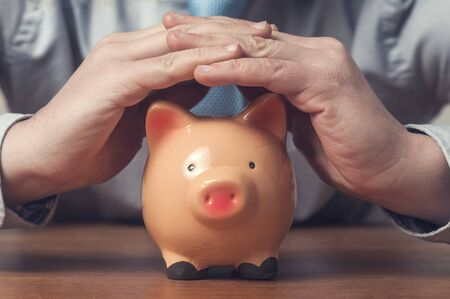 Protect savings: businessman in shirt and tie cover a piggy bank with his hands