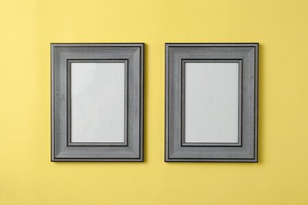 Two blank grey wooden photo frame on yellow background Stockfoto