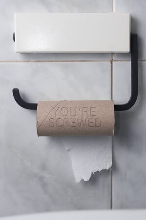 Finished roll of toilet paper with the inscription: you're screwed on a tiled bathroom