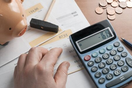 Economic crisis concept: calculator over a pile of household bills shows a negative balance. Image completed by some coins and a piggy bank